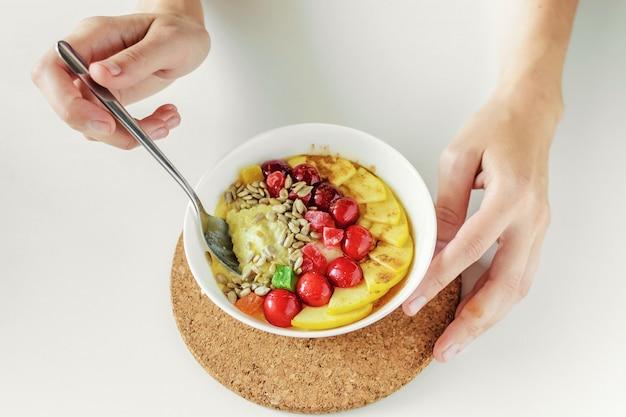 Ciotola di hite con porridge o muesli con semi, frutta fresca e secca e miele nelle mani delle donne