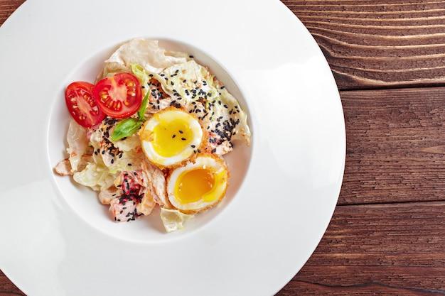 Ciotola di insalata di uova alla diavola su fondo di legno scuro