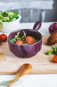 Ciotola di insalata di verdure fresche e ingredienti per cucinare sul tavolo della cucina