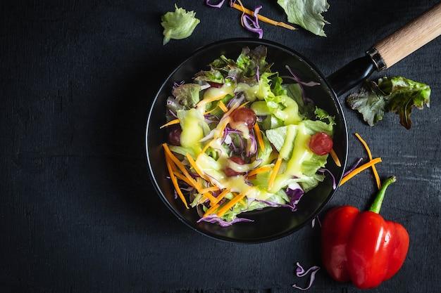 Ciotola di insalata di verdure su sfondo nero.