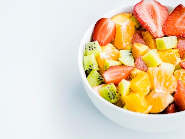 Ciotola di insalata luminosa di frutta fresca su sfondo bianco