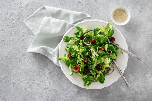 Ciotola di insalata verde con foglie di mache e pomodori al forno