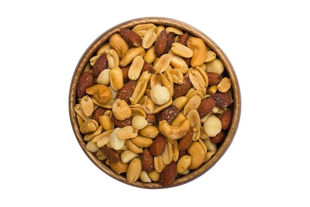 Ciotola di legno con noci miste su uno sfondo bianco. cibo e spuntini sani. noci, pistacchi, mandorle, nocciole e anacardi