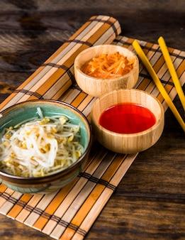 Ciotola di legno di carota grattugiata; salsa di peperoncino e fagioli germogliati sopra la tovaglietta con le bacchette