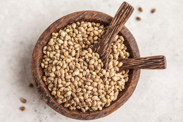 Ciotola di legno di semi di canapa non trattati. sfondo bianco, vista dall'alto.