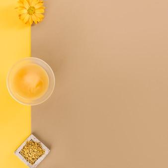 Ciotola di limone cagliata; semi di polline d'api e fiori su sfondo colorato doppio