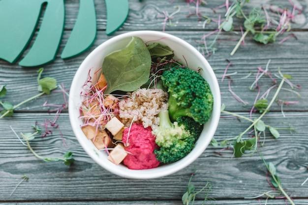 Ciotola di luminoso pranzo vegano sano: insalata di verdure con tofu, hummus e broccoli