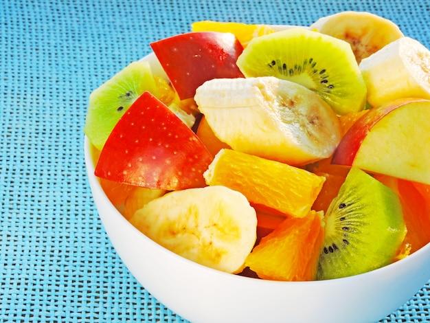 Ciotola di macedonia. insalata di frutta con kiwi, banana, arancia e mela. concetto di fitness food.