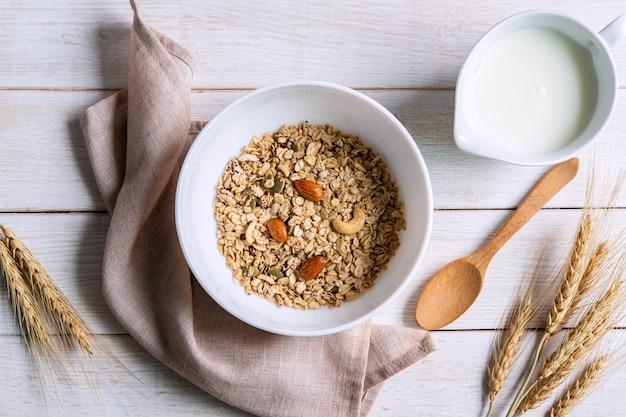 Ciotola di mandorla di granola e grani sulla tavola di legno bianca, prima colazione sana