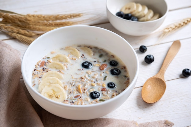 Ciotola di mandorla e granelli di granola con il mirtillo e la banana sulla tavola di legno, prima colazione sana