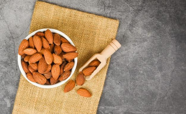 Ciotola di mandorle sul sacco / close up mandorle noci alimenti naturali proteine e snack