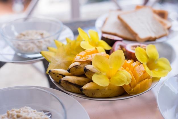 Ciotola di mango, banana, frutto della passione condita con fiori e frutta fresca