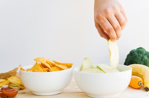 Ciotola di mela vista dall'alto vs nachos ciotola