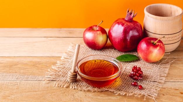 Ciotola di miele ad alto angolo con mestolo e frutta