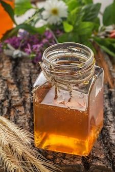 Ciotola di miele con mestolo e miele che scorre