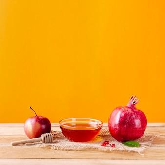 Ciotola di miele vista frontale con mestolo e frutta