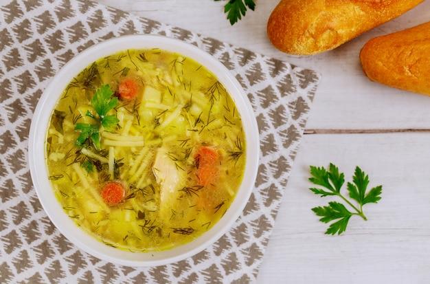Ciotola di minestra di pasta di pollo con pane