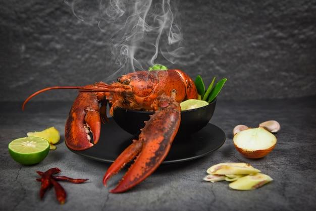 Ciotola di minestra piccante dell'aragosta rossa frutti di mare cucinati con la tavola di cena dell'aragosta e gli ingredienti delle spezie sull'alimento tailandese della banda nera