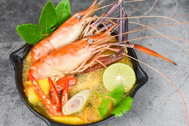 Ciotola di minestra piccante di gamberi con ingredienti di spezie su oscurità - frutti di mare cotti con tavolo da pranzo di zuppa di gamberetti cibo tailandese tradizionale asiatico, tom yum kung