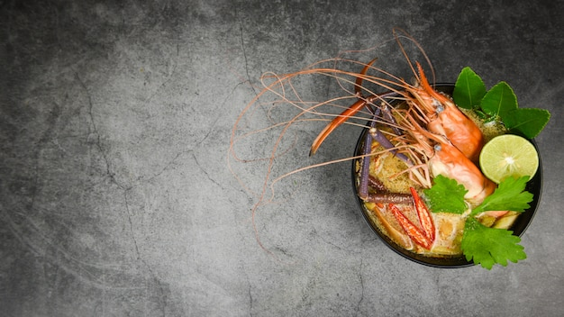 Ciotola di minestra piccante di gamberi con ingredienti di spezie su scuro frutti di mare cotti con tavolo da pranzo di zuppa di gamberetti cibo tailandese tradizionale asiatico, tom yum kung