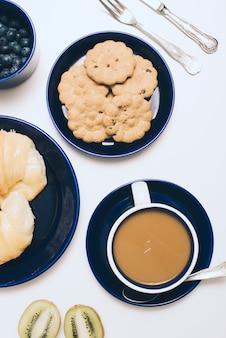 Ciotola di mirtilli; biscotti; tazza di caffè e kiwi su sfondo bianco