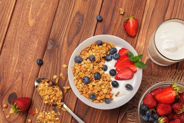 Ciotola di muesli casalingo con yogurt e frutti di bosco freschi su fondo di legno
