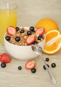 Ciotola di muesli con fragole, ribes nero e succo d'arancia