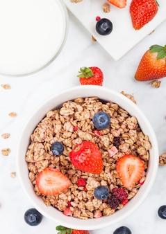 Ciotola di muesli di cereali sani con fragole e mirtilli e bicchiere di latte sul bordo di marmo