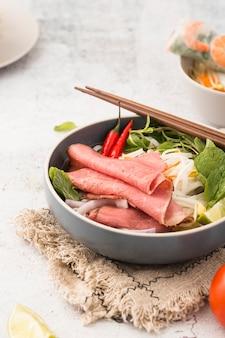 Ciotola di noodles con prosciutto e gamberi