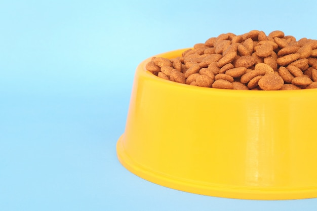 Ciotola di plastica gialla piena con cibo per cani