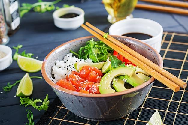 Ciotola di poke di pesce salmone hawaiano con riso, avocado, paprika, semi di sesamo e lime.