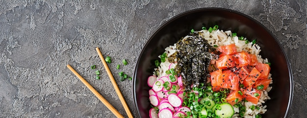 Ciotola di poke di pesce salmone hawaiano con riso, ravanello, cetriolo, pomodoro, semi di sesamo e alghe. ciotola di buddha. dieta alimentare. vista dall'alto. disteso.