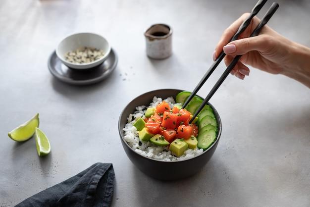Ciotola di poke hawaiana delle bacchette di cibo della mano della donna con i salmoni, il riso, l'avocado ed il cetriolo. dieta alimentare.