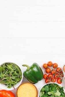 Ciotola di polenta e verdure a foglia sulla scrivania in legno bianco
