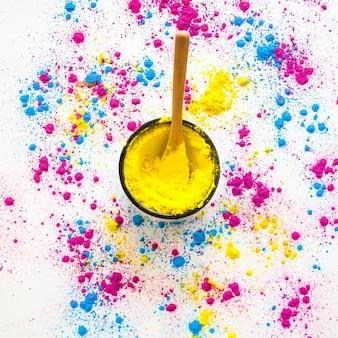 Ciotola di polvere gialla di holi con il cucchiaio su fondo bianco