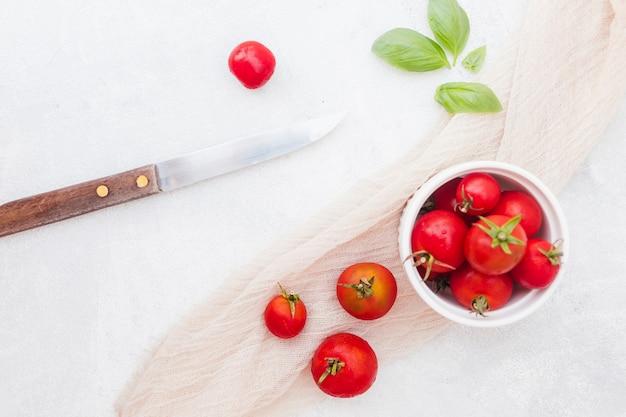 Ciotola di pomodorini rossi con foglie di basilico; sciarpa e coltello affilato