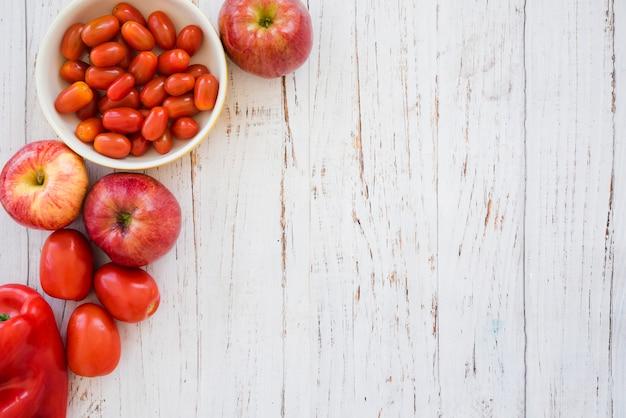 Ciotola di pomodorini rossi; mela e peperone su sfondo bianco strutturato