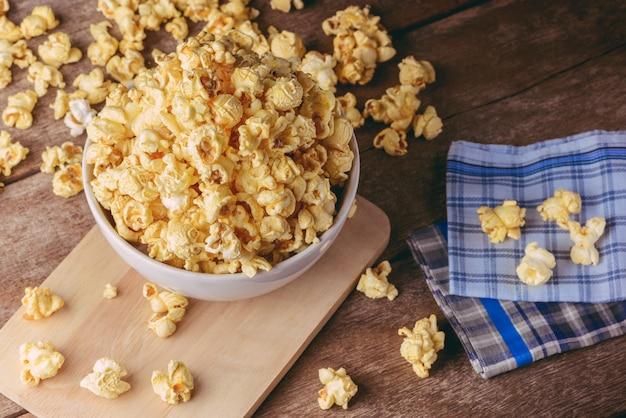 Ciotola di popcorn sulla tavola di legno, fuoco selettivo