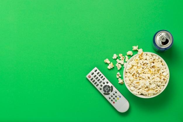 Ciotola di popcorn, un telecomando della tv, una lattina con un drink su uno sfondo verde. concetto di guardare la tv, film, serie tv, sport, spettacoli a tuo piacimento.