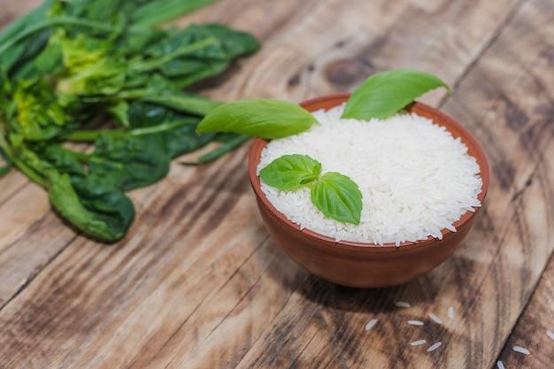Ciotola di riso con foglie di basilico sul tavolo di legno