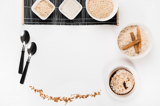 Ciotola di riso cruda con il cucchiaio e riso della salsa di soia su fondo bianco