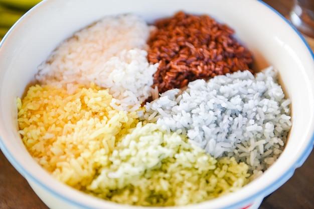 Ciotola di riso variopinta del gelsomino / alimento della bacca del riso cucinato riso giallo verde blu e bianco marrone
