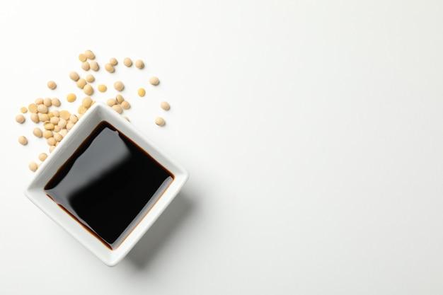 Ciotola di salsa di soia, semi di soia su sfondo bianco, spazio per il testo. vista dall'alto
