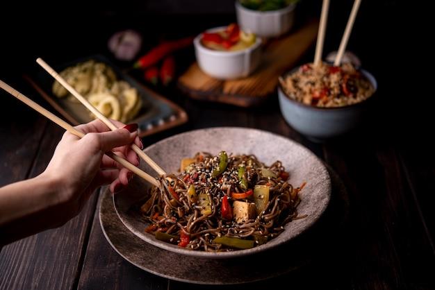 Ciotola di tagliatelle con verdure e altri alimenti asiatici