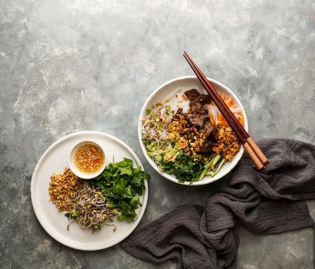 Ciotola di tradizionale insalata di pasta vietnamita - bun bo nam bo, con carne di manzo, spaghetti di riso, erbe fresche, verdure in salamoia e salsa di pesce