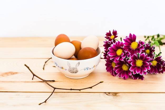 Ciotola di uova in ceramica, piatto di fondo in legno, preparazione per pasqua, prodotti agricoli, pollo e uova, decorazione della casa per le vacanze, rami degli alberi con gemme, primavera, bellissimo rosso brillante