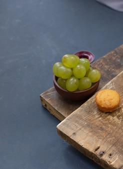Ciotola di uva verde e un muffin alla vaniglia sul pezzo di legno