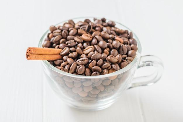 Ciotola di vetro con chicchi di caffè e stecca di cannella sulla tavola di legno bianca. cereali per la preparazione della bevanda popolare.