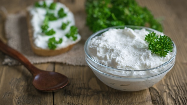 Ciotola di vetro con crema di cagliata, pane e prezzemolo su una tavola di legno d'annata.