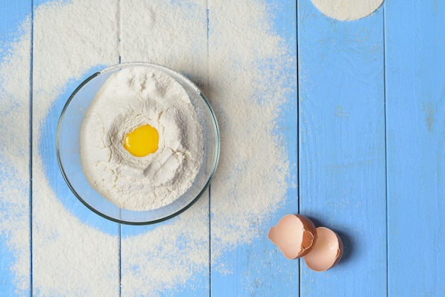 Ciotola di vetro con farina, gusci d'uovo e tuorlo d'uovo nella farina